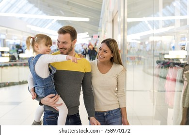 Happy family with child doing shopping together in the shopping mall