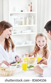 A happy family with a child eat breakfast in the kitchen