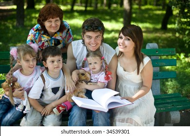 Happy family with  child and grandmother in outdoor read book. Upbringing.