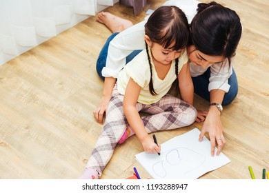 Happy family child kid girl kindergarten drawing teacher education mother mom with beautiful mother at interior room home