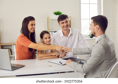 Happy family with child meeting with manager at real estate agency. Smiling husband and wife shaking hands with agent and thanking him for help. Buying new house and signing purchase agreement concept