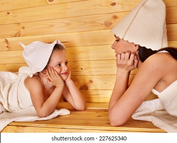 Happy family with child relaxing at sauna.