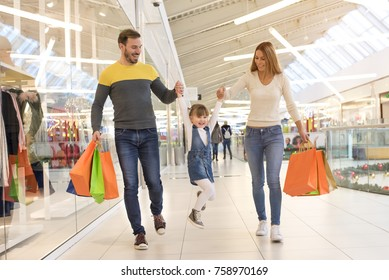 Happy family with child and shopping bags walking along the shopping mall