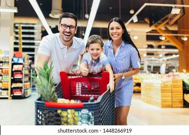 Glückliche Familie mit Kind und Einkaufswagen kaufen Lebensmittel im Lebensmittelgeschäft oder Supermarkt