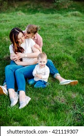 Happy family with a child sitting on the grass on a summer day. family walking outdoor