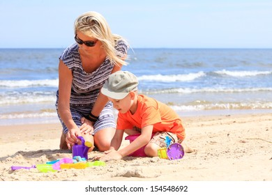 Happy family child son and mother playing toys on beach sea background