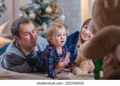 Happy family with a child spend Christmas together. Parents and daughter play at home near the Christmas tree.