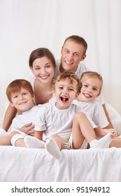 Happy family with children in the bedroom
