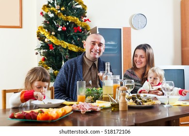 Happy family with children celebrating Christmas over celebratory table at home interior