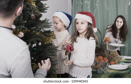 Happy family with children decorating Christmas tree at home