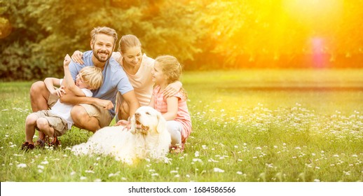 Happy family with children and dog together in the garden in summer