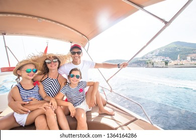 Happy family with children enjoy relaxing on a yacht at sea