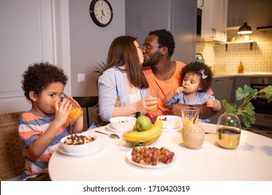 Happy family with children having Breakfast in the kitchen at a large table, dad and mom kissing
