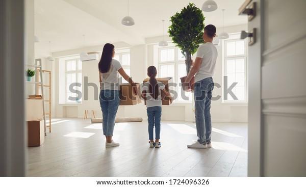 Gute Familie mit Kindern, die mit Kisten in einem neuen Appartementhaus umziehen. Rückansicht.