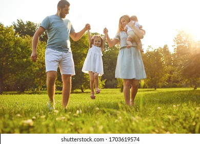 Happy family with children in the park at sunset.