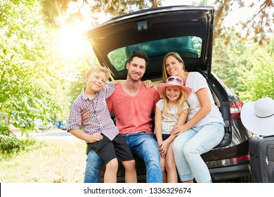 Happy family with children is sitting at the car in the summer
