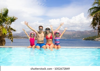 happy family with children sitting on the edge of the pool in a tropical seaside resort against the backdrop of the sea and palms