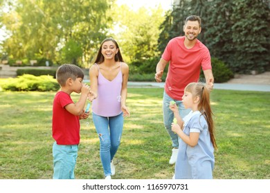 Happy family with children spending time together in green park on sunny day