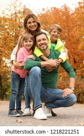 Happy family with children spending time together in park. Autumn walk