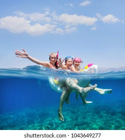 happy family with children is swimming and having fun in the sea on an inflatable mattress. View with above and below water