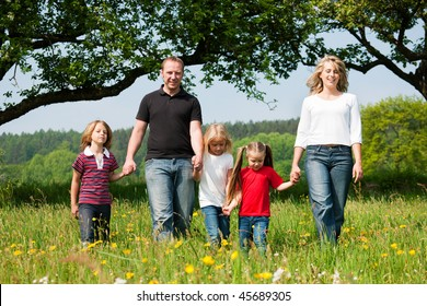 Happy family with Children walking down a meadow with dandelion flowers at a bright spring day