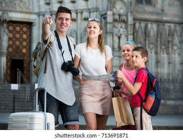 Happy family with children walking in European city with map