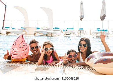 Happy family with children wearing sunglasses swimming in pool with rubber ring during travel or vacation
