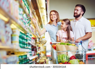 Happy family choosing dairy products in supermarket