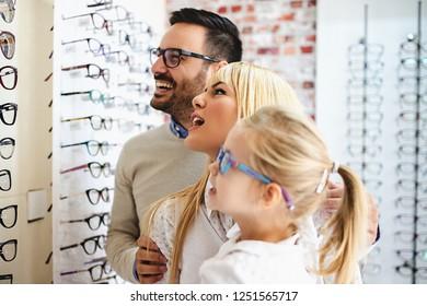 Happy family choosing glasses in optics store.