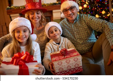 Happy family with Christmas gift at home together