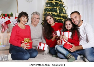 Happy family with Christmas presents in living room