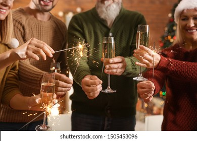 Happy family with Christmas sparklers and glasses of champagne at home