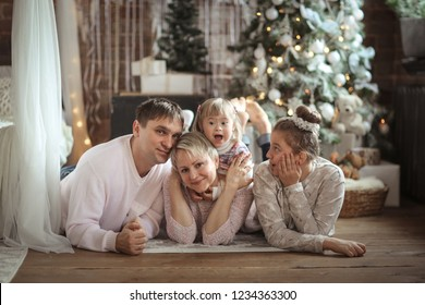 happy family at the Christmas tree, two children - a teenager and a Toddler with Down syndrome.