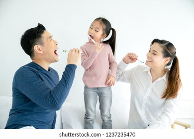 Happy family cleaning teeth with toothbrushes together , concept health care teeth.