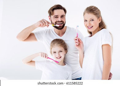 Happy family cleaning teeth with toothbrushes together isolated  on white