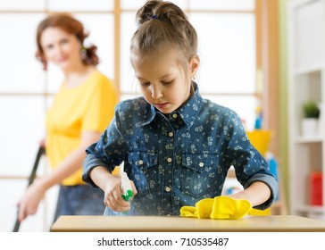 Happy family cleans the room. Mother and her child daughter do the cleaning in the house. A woman and a little kid girl wiped the dust and vacuumed the floor.