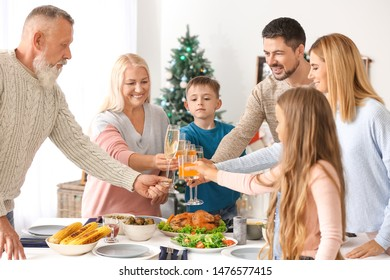 Happy family clinking glasses during Christmas dinner at home