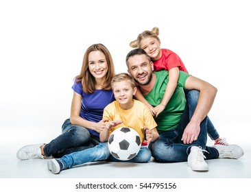 Happy family in colored t-shirts sitting together with soccer ball isolated on white