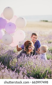 Happy family with colorful balloons posing in a lavender field. Summer mood
