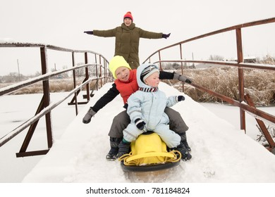 A happy family in colorful clothes posing in front of a photographer with a new yellow sled. Picturesque area with a bridge on the river. The concept of winter vacations, Christmas, New Year.
