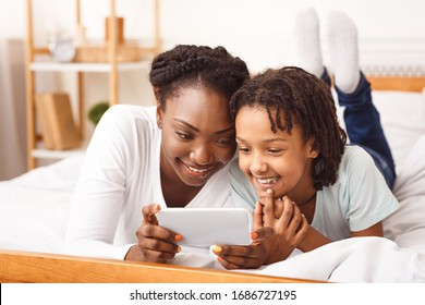 Happy Family Concept. African mother and her daughter playing in bedroom, having fun with phone