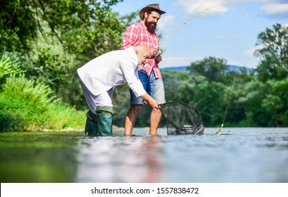 Happy family concept. Catching and fishing concept. Two male friends fishing together. fly fish hobby of businessman. retirement fishery. happy fishermen friendship. retired dad and mature son.