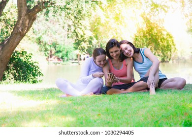 Happy family concept: Charming beautiful mother play and shows some funny photo or family's photo on mobile phone. They're laughing with it. Family enjoy their life and feels relaxed, sit near river
