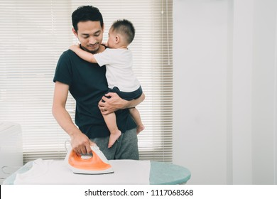 Happy family concept, Father pick up little son his ironing clothes on ironing board doing chores at home in holidays weekend.