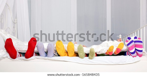 Happy family concept. Feet of father, mother and four children in colorful knitted socks on white bed. Family sleeping together.