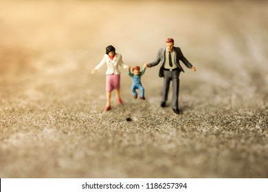 Happy Family Concept. Miniature Figure of Father, Mother and Son Walking Outdoor to Making Activities together