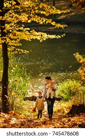 Happy family concept. Mother and children having fun in the autumn forest next to a lake. Motherhood concept