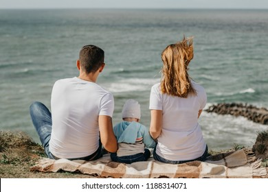 Happy family concept. Parents with baby sits on a cliff and looks at the ocean. Wonderful view.