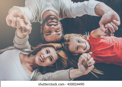 Happy family concept. Top view of happy family of three bonding to each other and smiling while lying on the hardwood floor