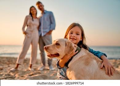 Fröhliches Familienkonzept. Junge attraktive Mutter, gut aussehender Vater und ihre kleine süße Tochter stehen zusammen am Strand mit Hund.